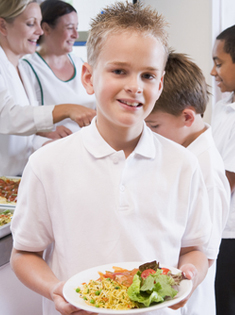 A school child with a plate of food